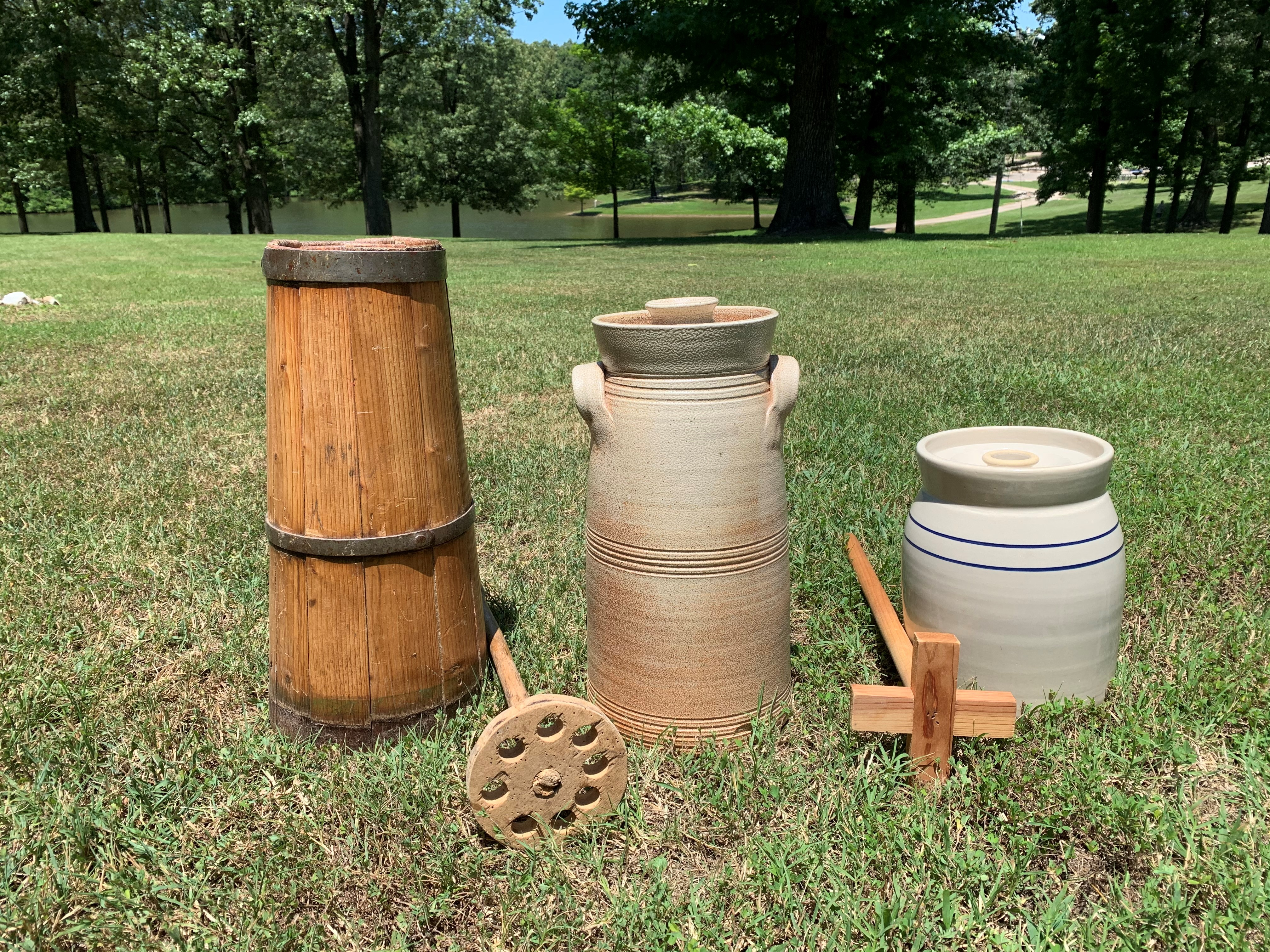 Three butter churns are lined up outside from tallest to shortest. The first churn is wooden and the other two are clay. There are two dashers (wooden stick used to churn the butter) in between the three churns. One dasher has a cross pattern and the other is a circle with holes in it.)