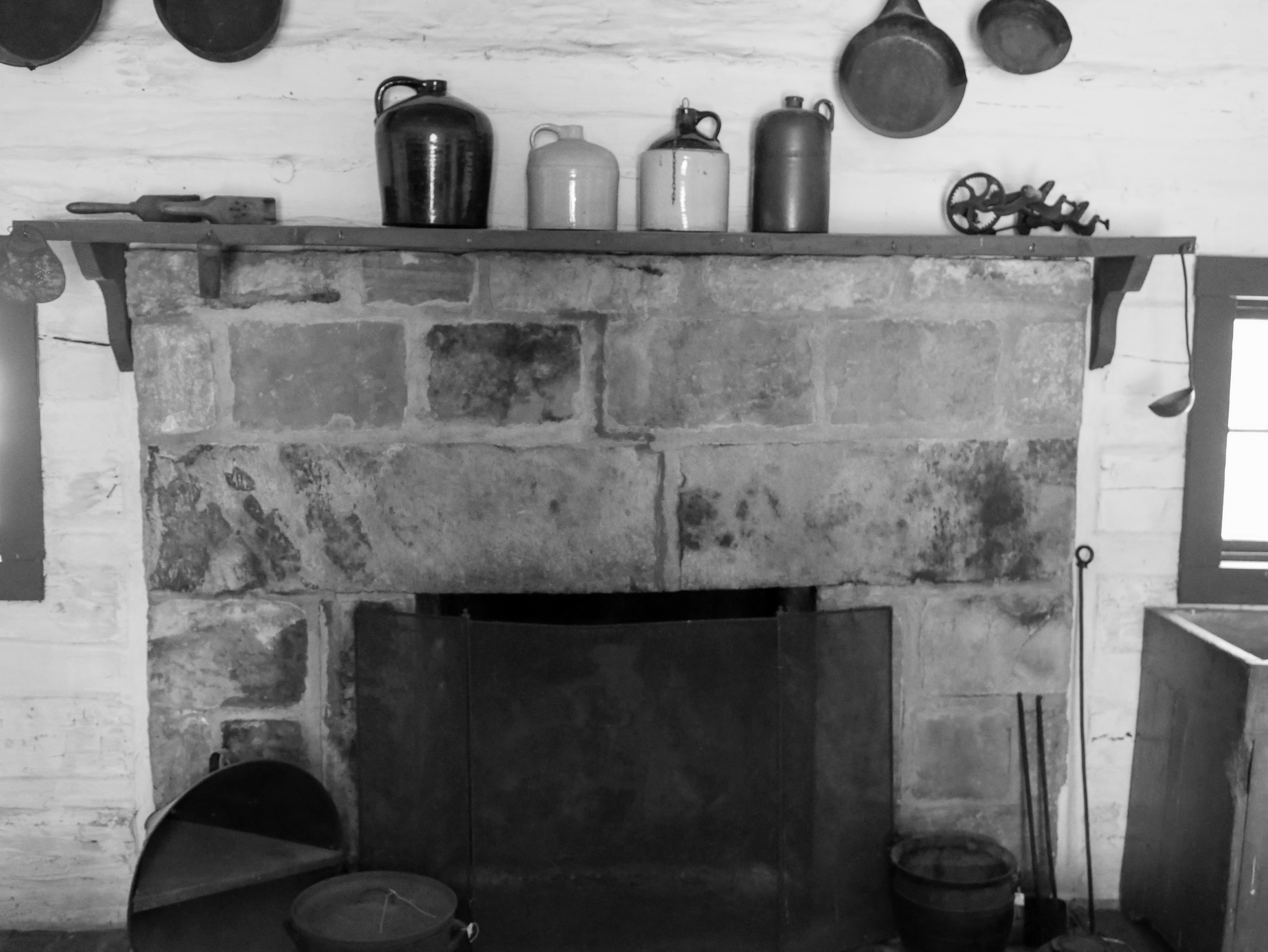 A large stone fireplace with iron screen is in the middle of the back wall of the kitchen. Several large iron Dutch ovens and fireplace utensils are set at each side. Atop the wooden mantle sit several large ceramic jugs. Iron skillets are hung barely out of frame above the fireplace.