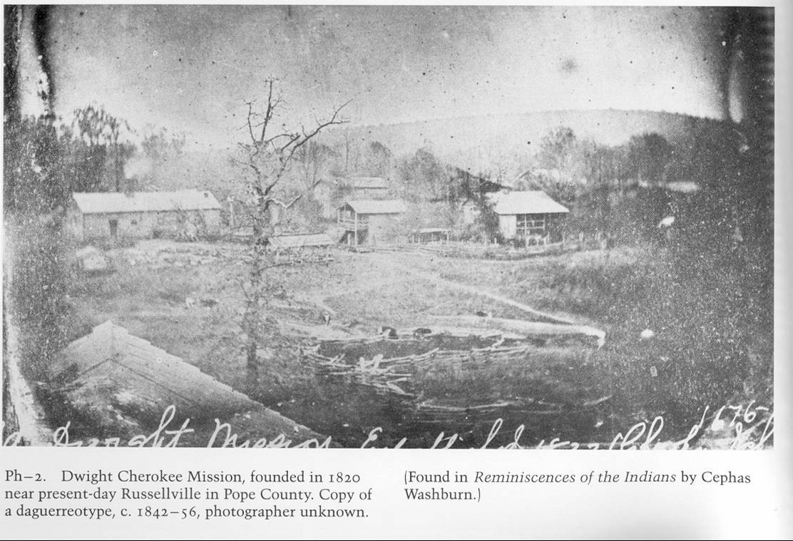Historic black and white photo of Dwight Cherokee Mission with several buildings. Caption on images says: Dwight Cherokee Mission, founded in 1820 near present-day Russellville in Pope County. Copy of a daguerreotype, c. 1842-56, photographer unknown. [Found in Reminiscences of the Indians by Cephas Washburn.]