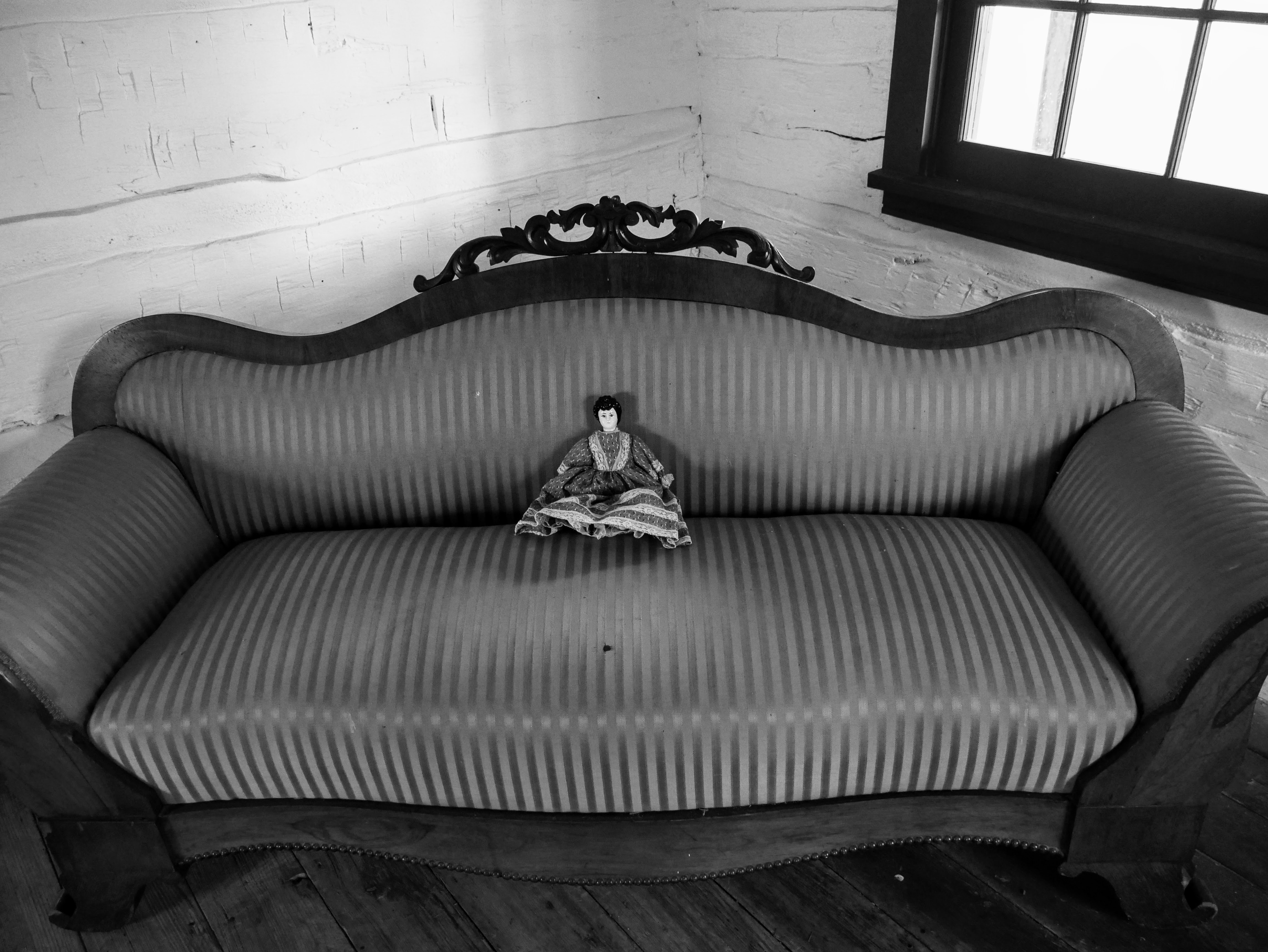 In the corner of a white-washed room, a wooden couch with striped upholstery is sat at an angle. A small ceramic doll in a fabric dress is in the middle of the couch.