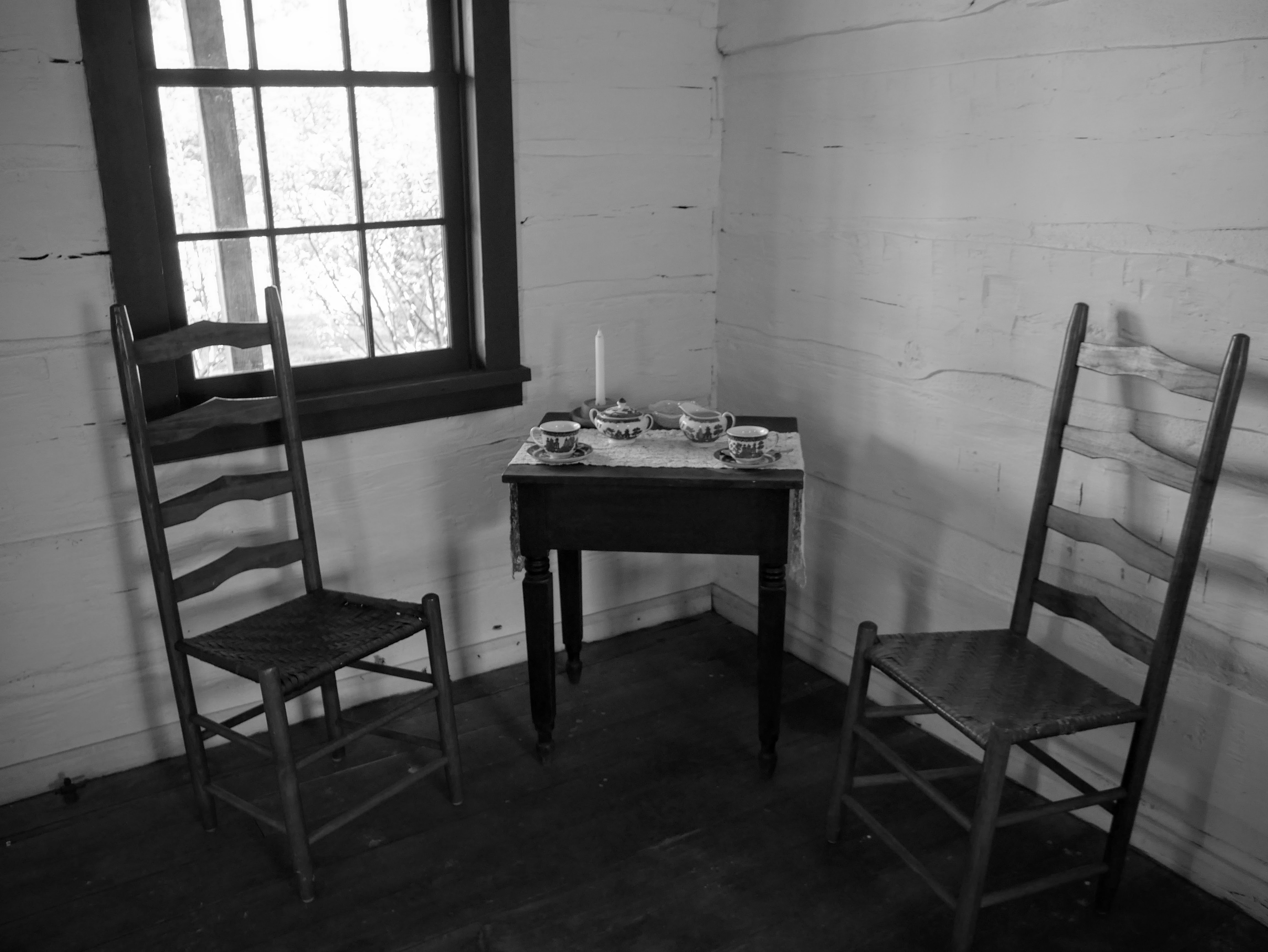 In the corner of a whitewashed room, two straight-backed chairs flank a small side table. Atop the table are two teacups, a sugar bowl, creamer, and one candle.