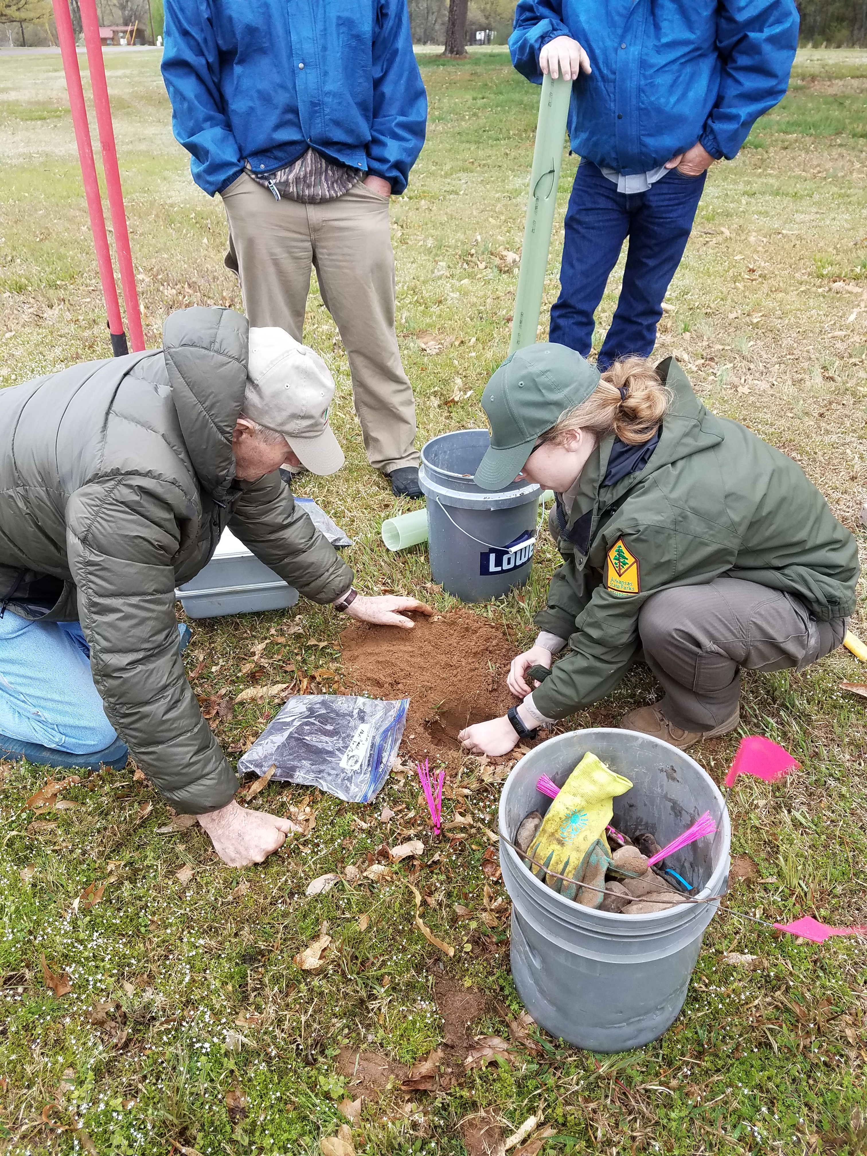 Park Interpreter Megan Ayres plants an Ozark chinquapin seed with the assistance of an OCF member at Lake Dardanelle State Park, while others observe.