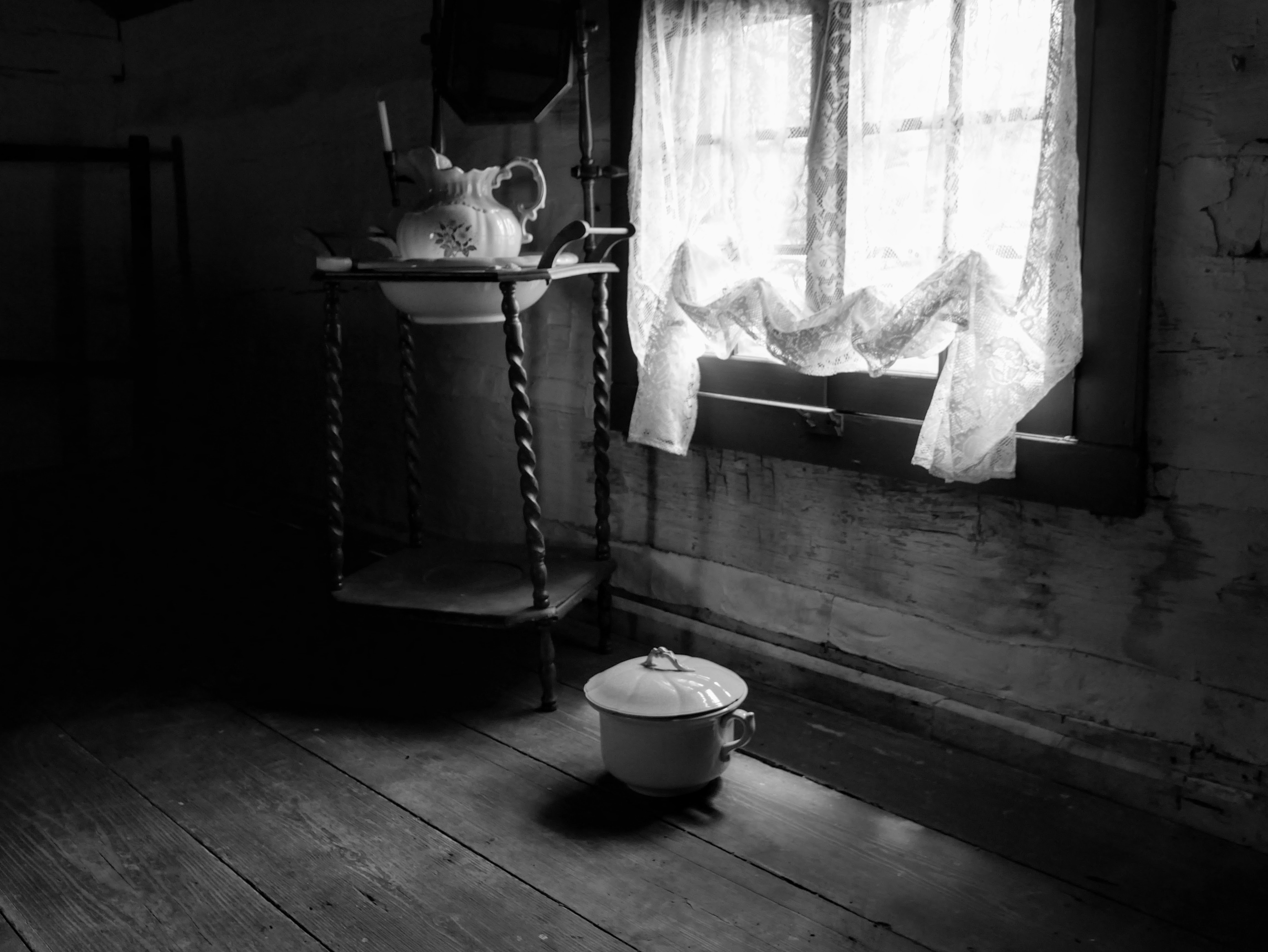 A small window with lace curtains illuminates a wooden washstand with mirror, bowl, and pitcher. On the wooden floor underneath the window sits a white, ceramic chamber pot with lid.