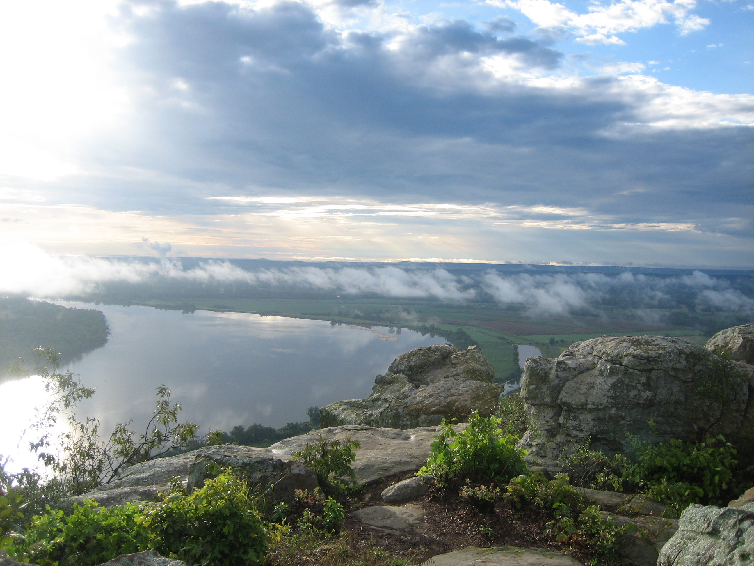 Sun peeking through the clouds shines down on the river as viewed from Petit Jean State Park. Photo Courtesy of Petit Jean State Park